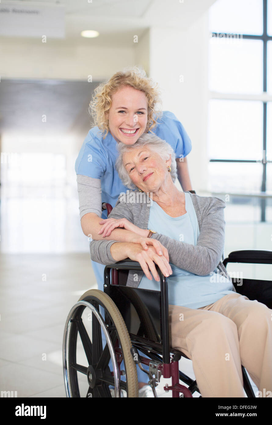 Portrait of smiling nurse and elderly patient in wheelchair - Stock Image