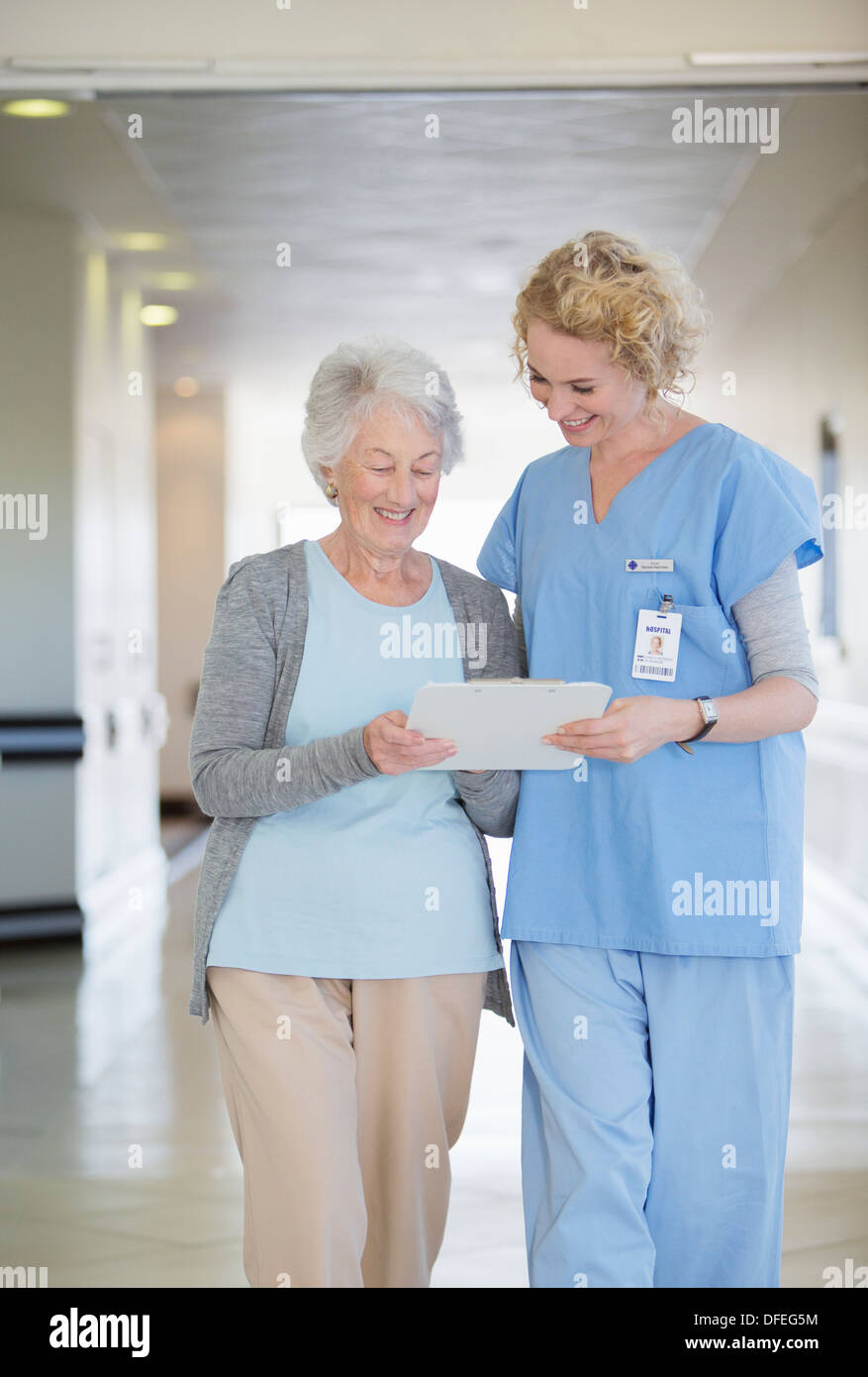 Nurse and aging patient reading chart in hospital corridor - Stock Image