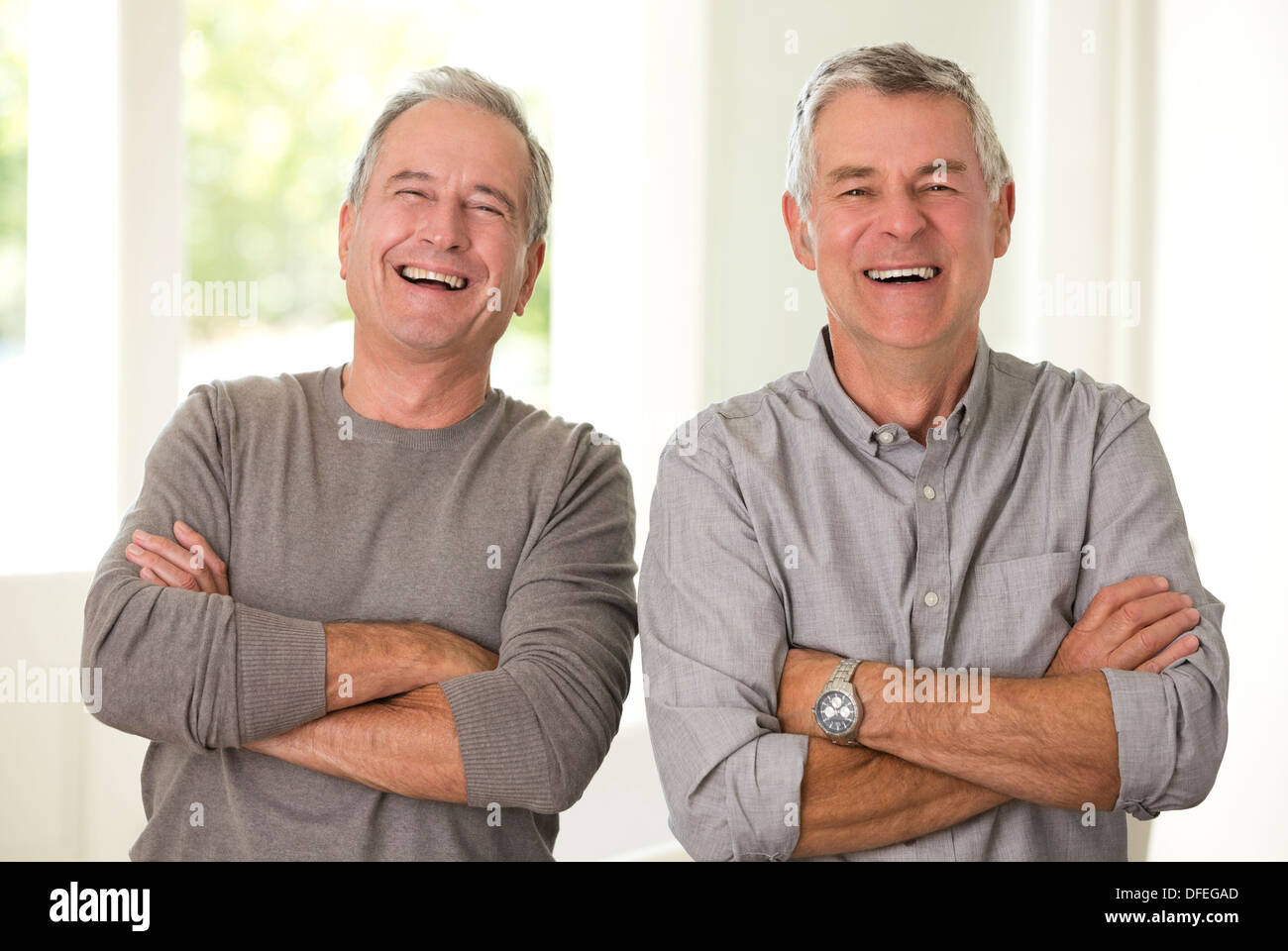 Portrait of senior men laughing with arms crossed - Stock Image