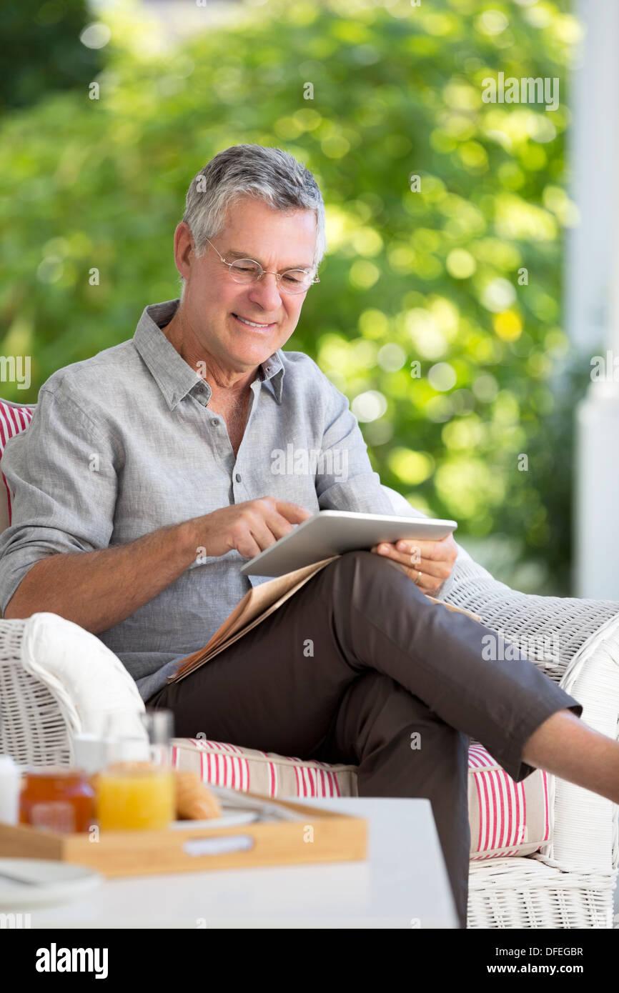 Senior man using digital tablet on patio - Stock Image