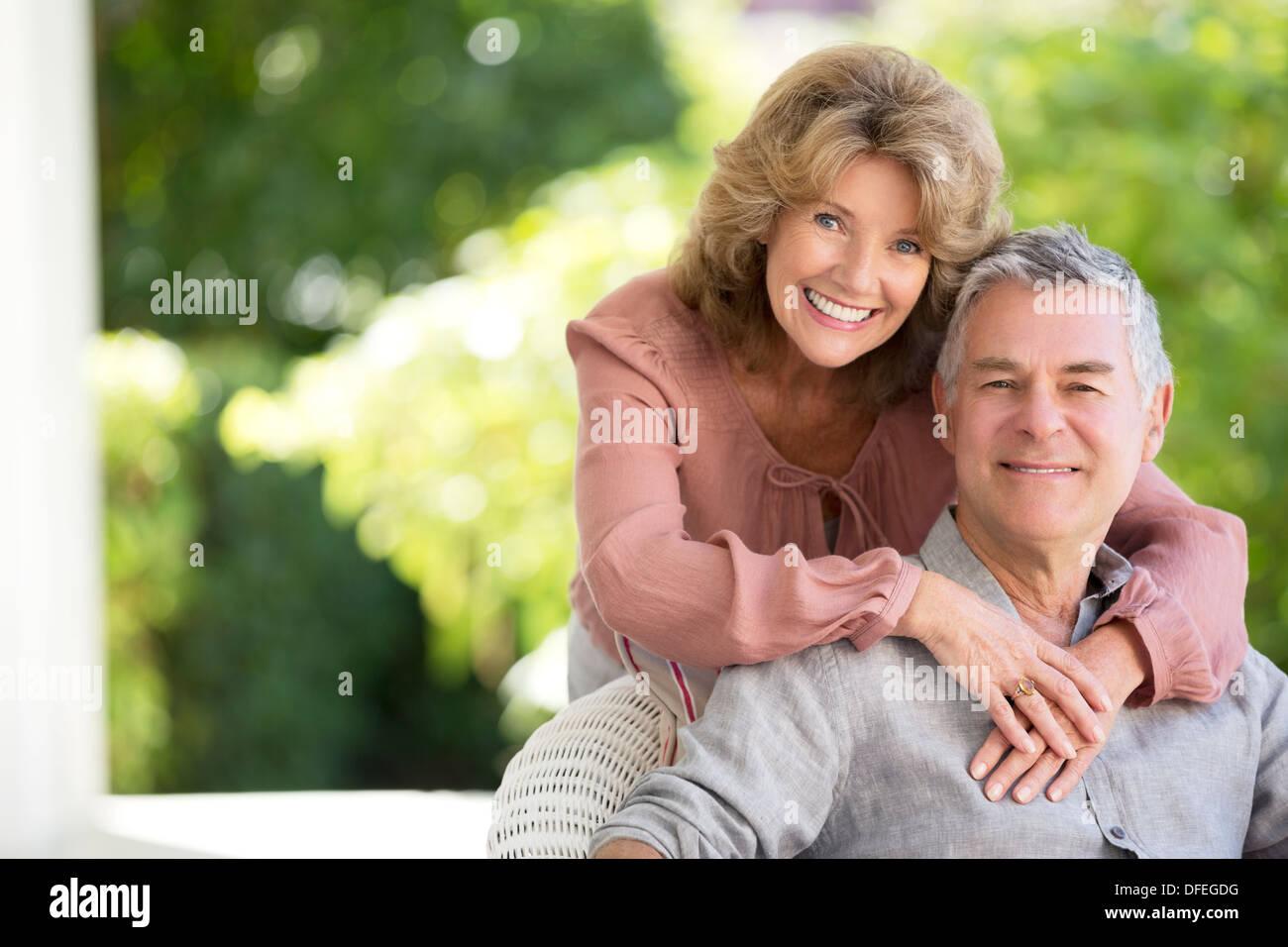 Senior couple hugging on patio Stock Photo