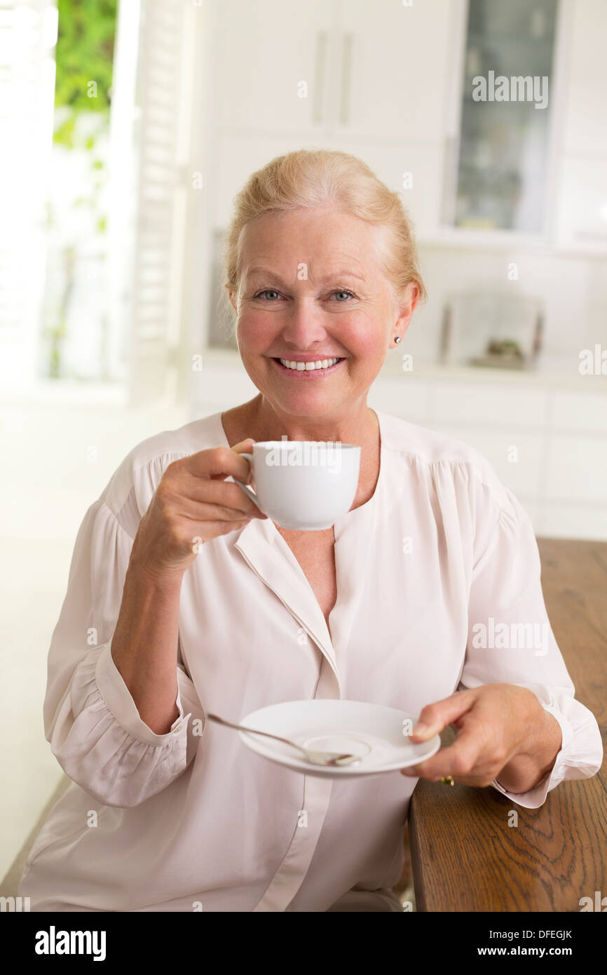 Portrait of senior woman drinking coffee - Stock Image
