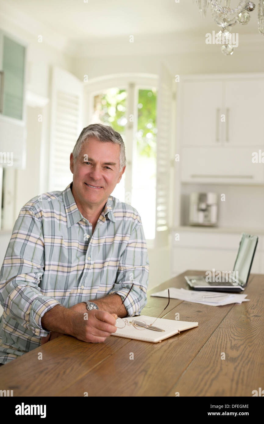 Portrait of senior man at kitchen table - Stock Image