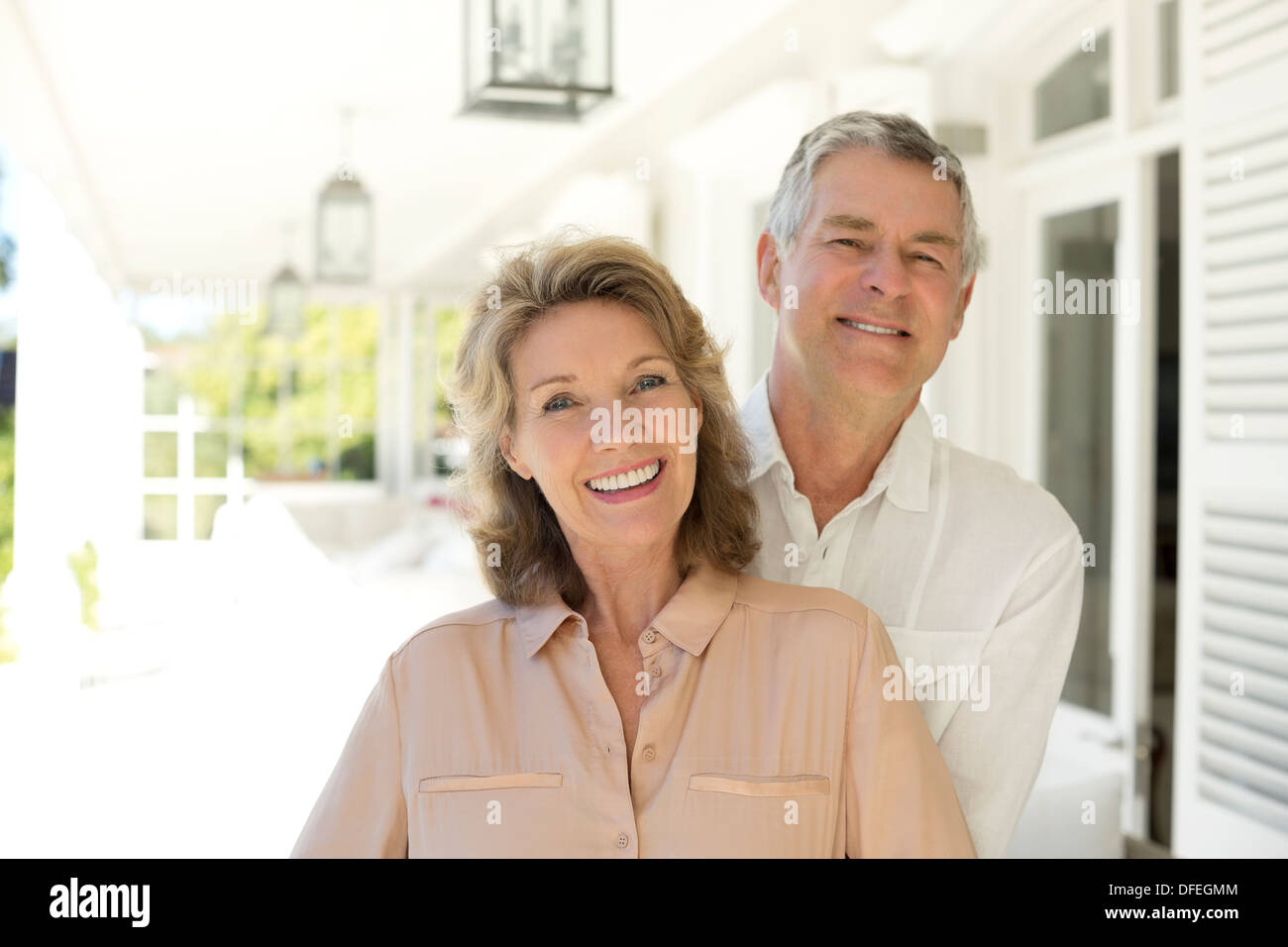 Portrait of senior couple smiling on porch - Stock Image