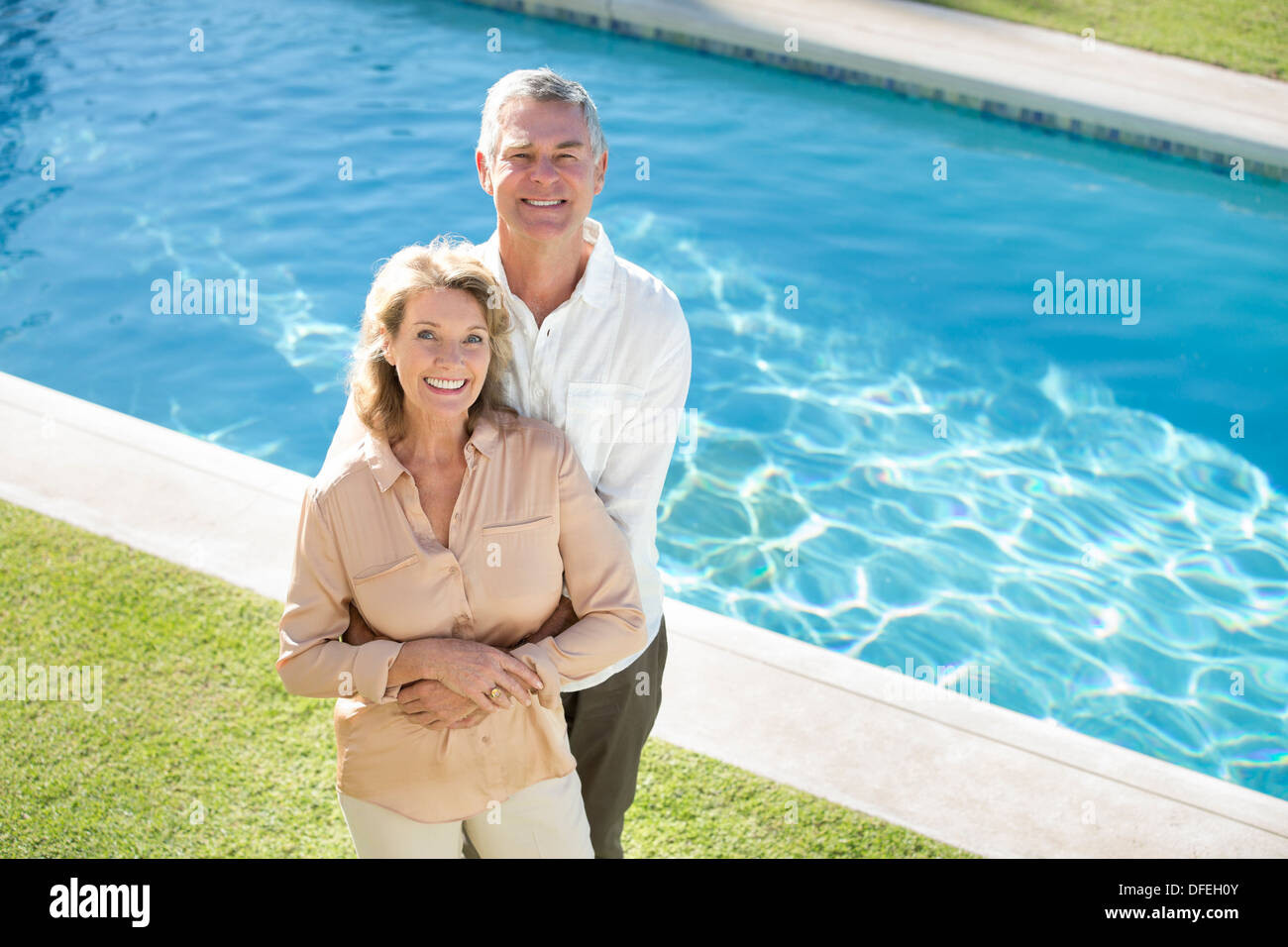Portrait of smiling senior couple at poolside - Stock Image