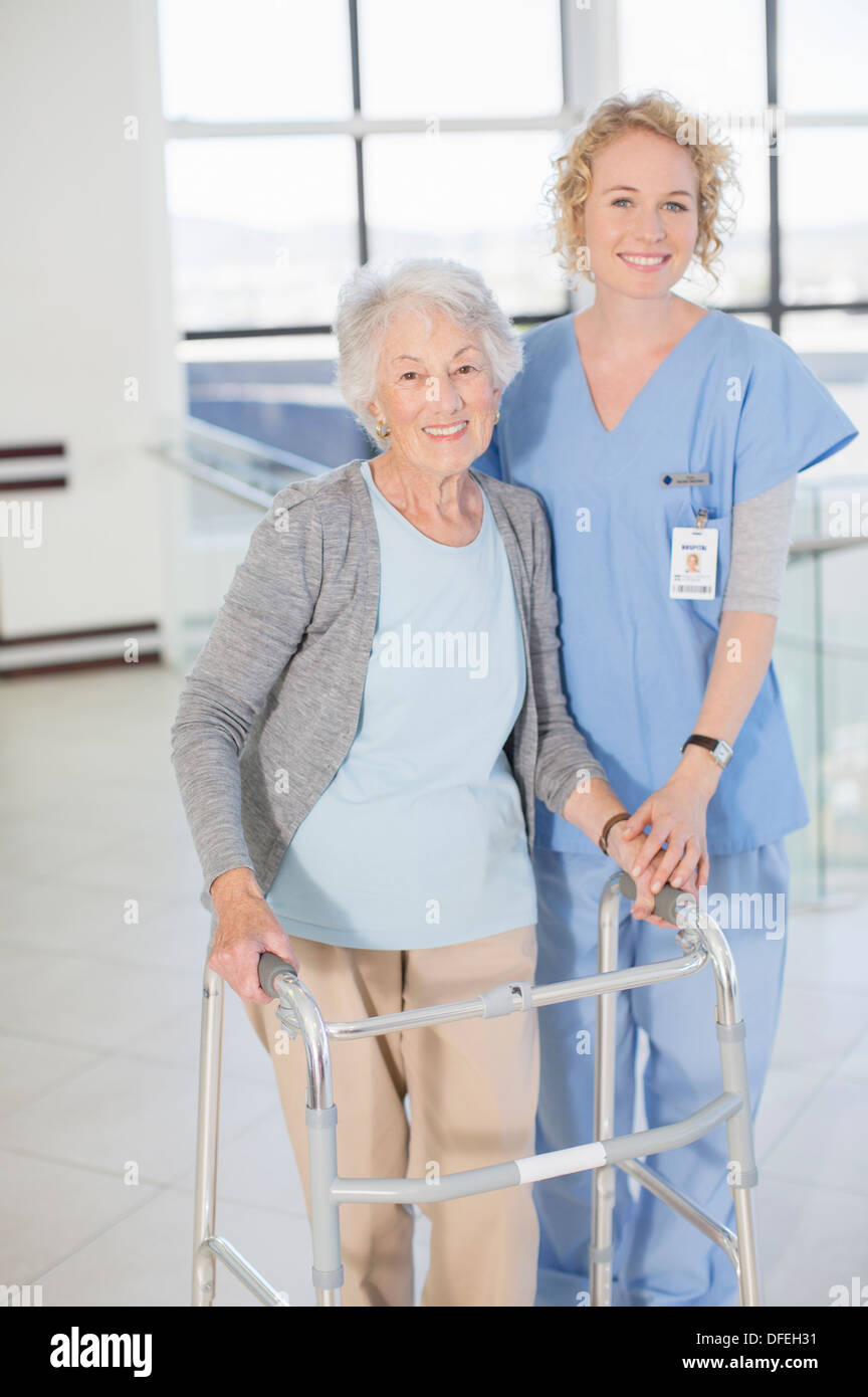 Portrait of smiling nurse and senior patient with walker - Stock Image