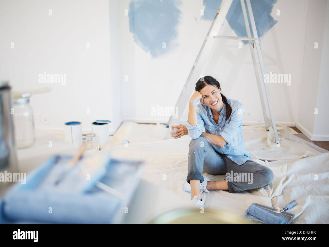 Portrait of woman surrounded by paint supplies - Stock Image