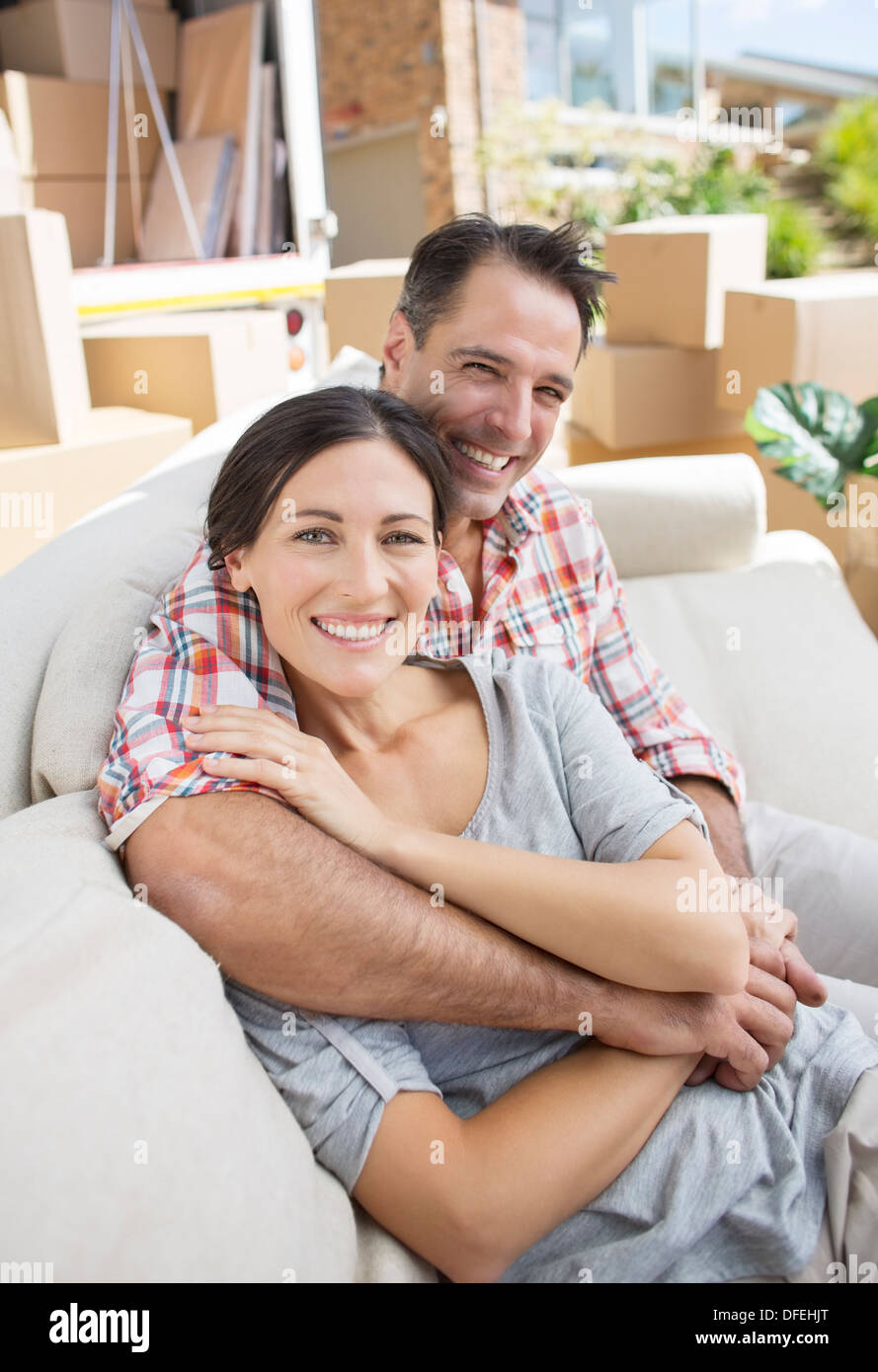 Portrait of smiling couple hugging on sofa in driveway near moving van - Stock Image