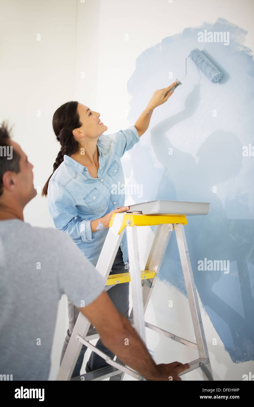 Couple painting wall blue - Stock Image