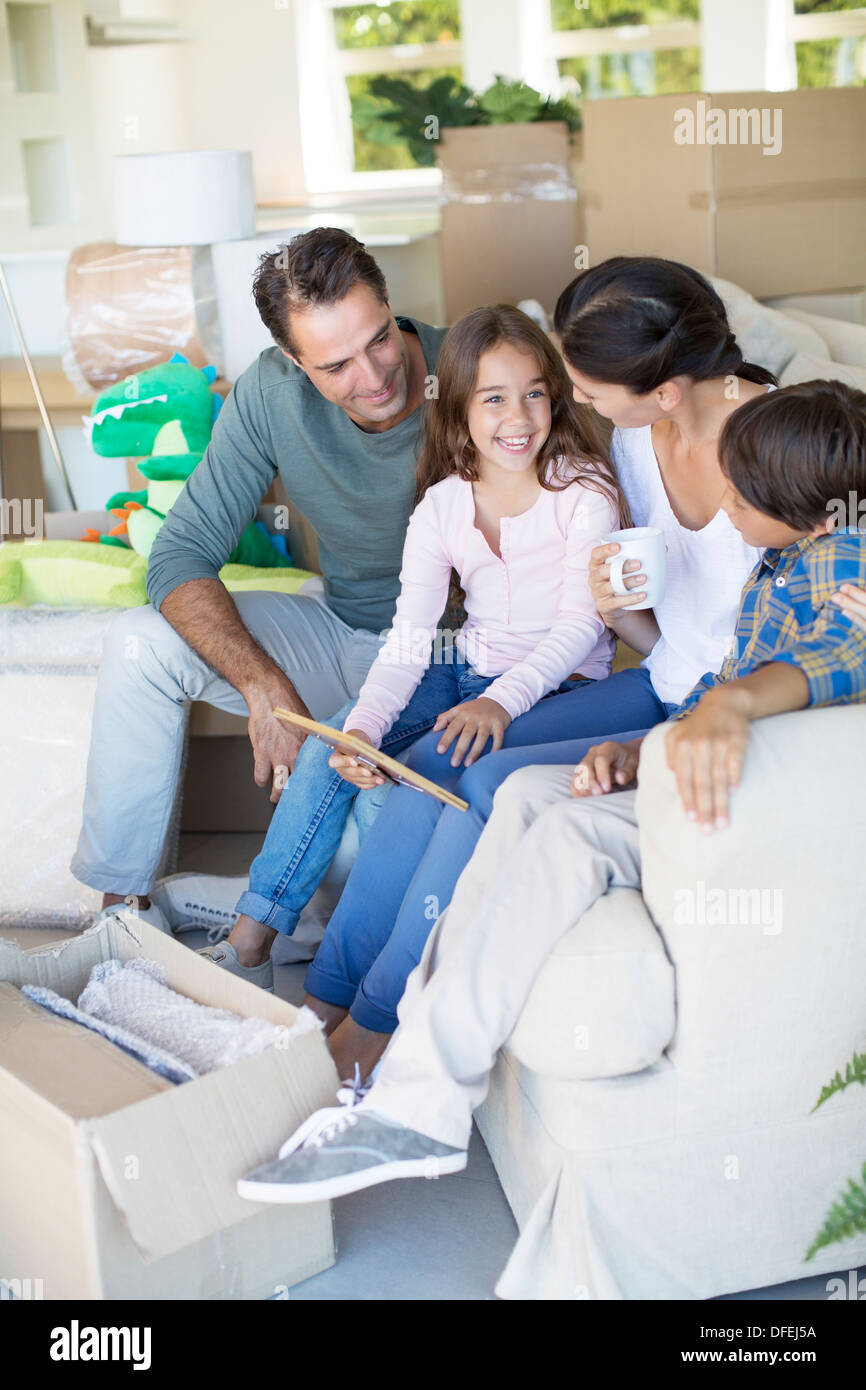 Family relaxing on sofa in new house - Stock Image