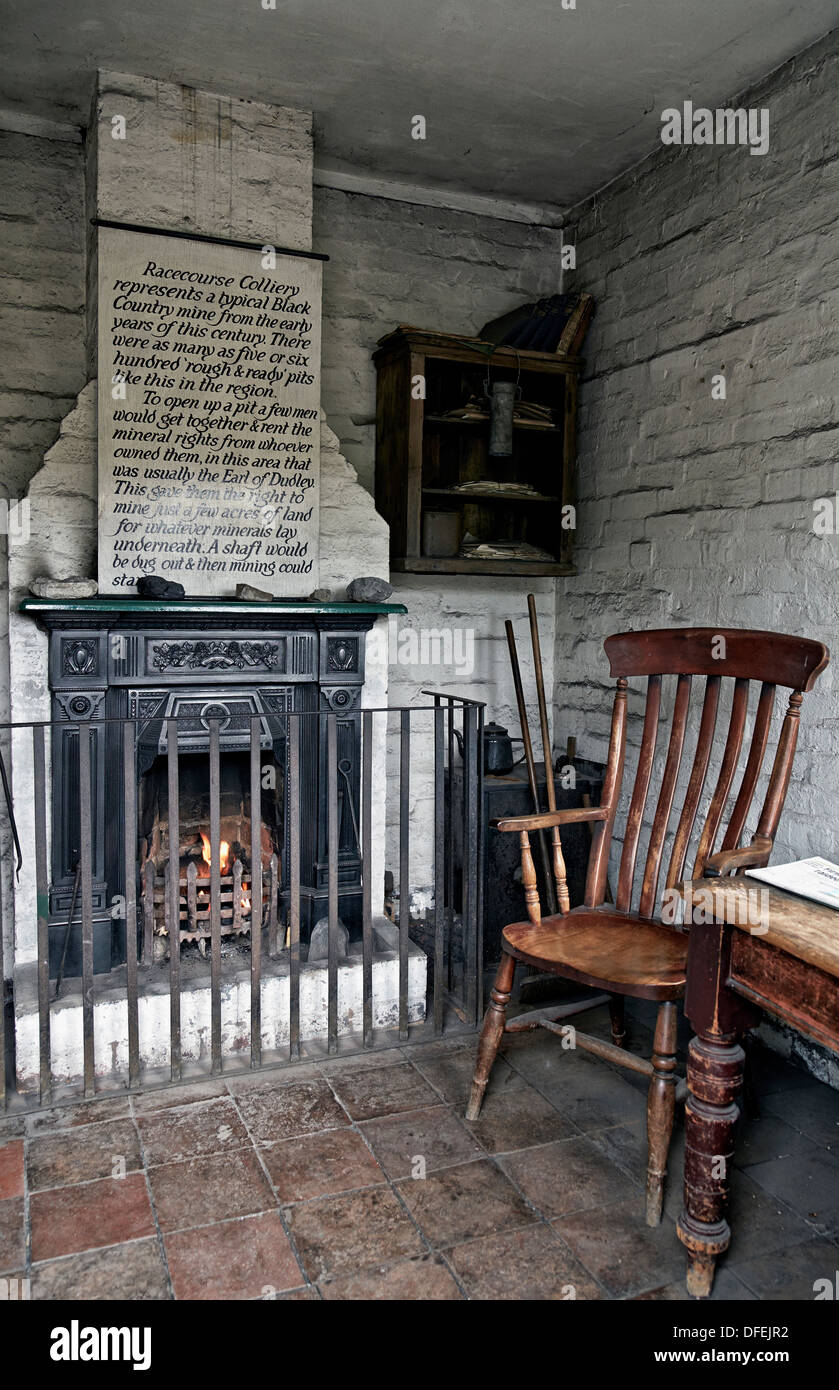 Fireplace and chair in a preserved 1800's/early 1900's cottage type home at The Black Country Living Museum Dudley England UK - Stock Image