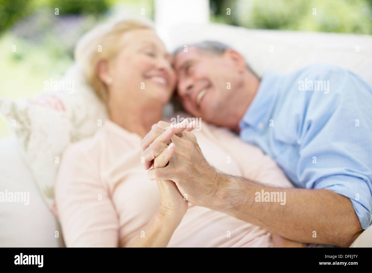 Senior couple holding hands on sofa - Stock Image