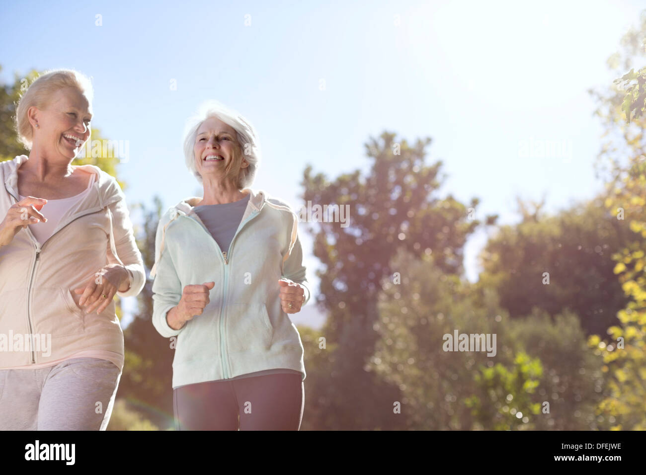 Senior women running outdoors - Stock Image