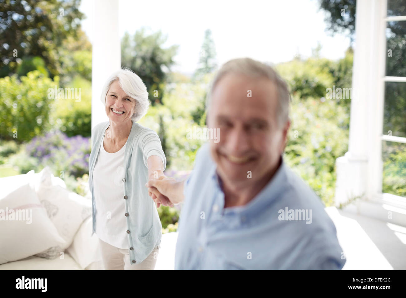 Senior couple holding hands on patio - Stock Image