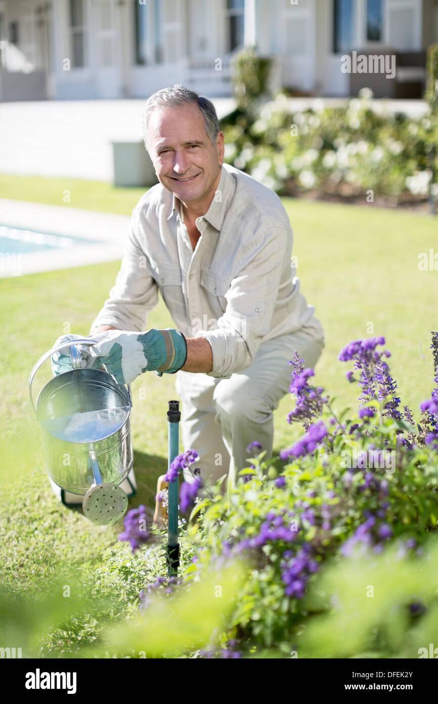 Senior man watering plants in garden - Stock Image