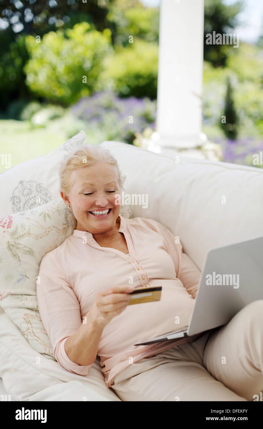 Senior woman shopping online on patio sofa - Stock Image