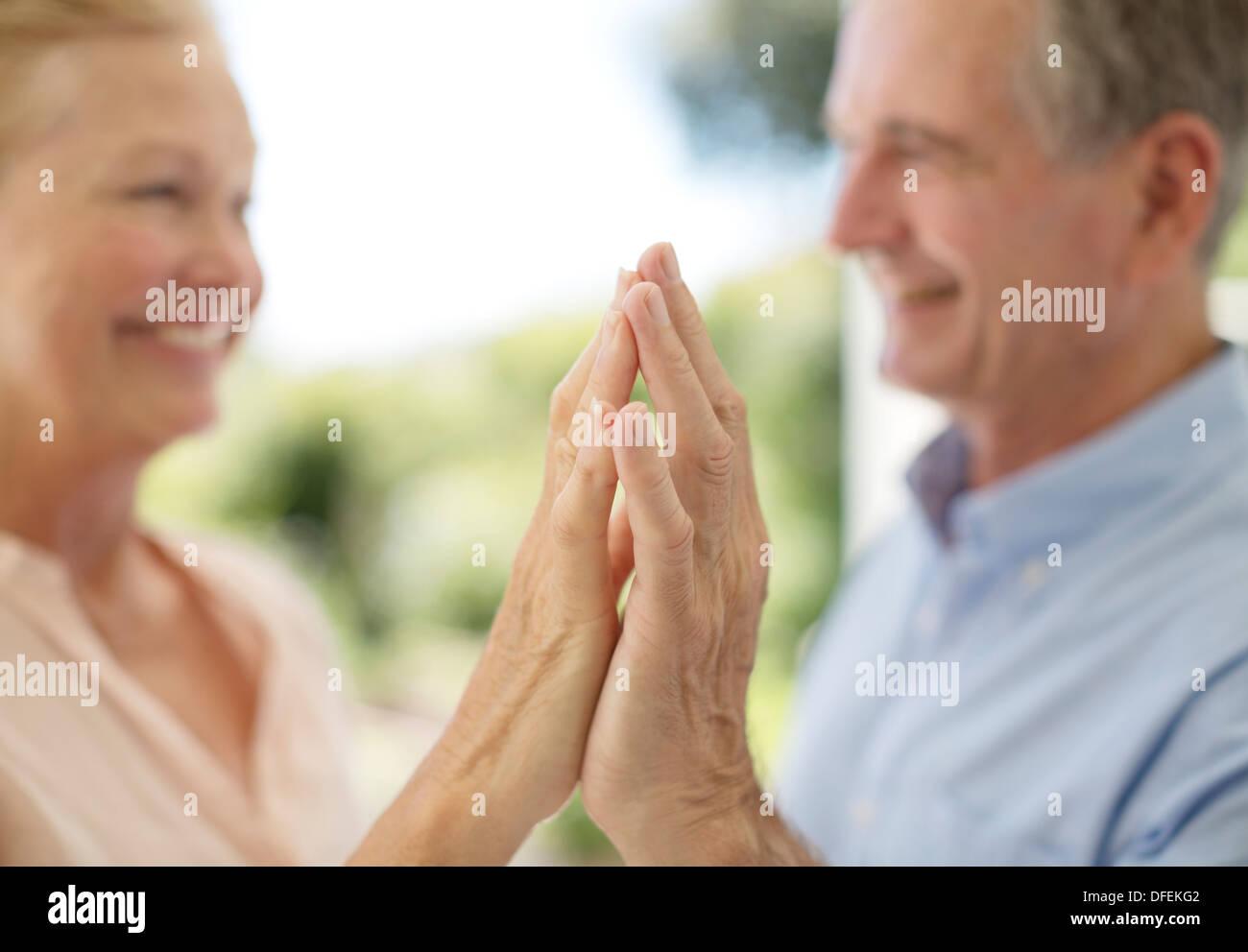 Senior couple touching hands on patio - Stock Image
