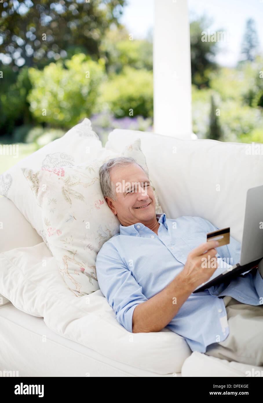 Senior man shopping online on patio sofa - Stock Image