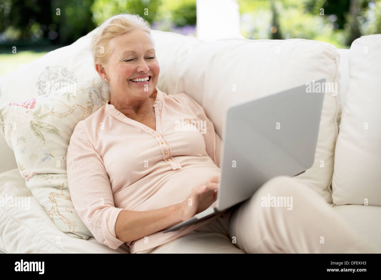 Senior woman using laptop on sofa - Stock Image