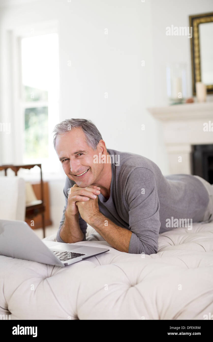 Senior man using laptop in livingroom - Stock Image