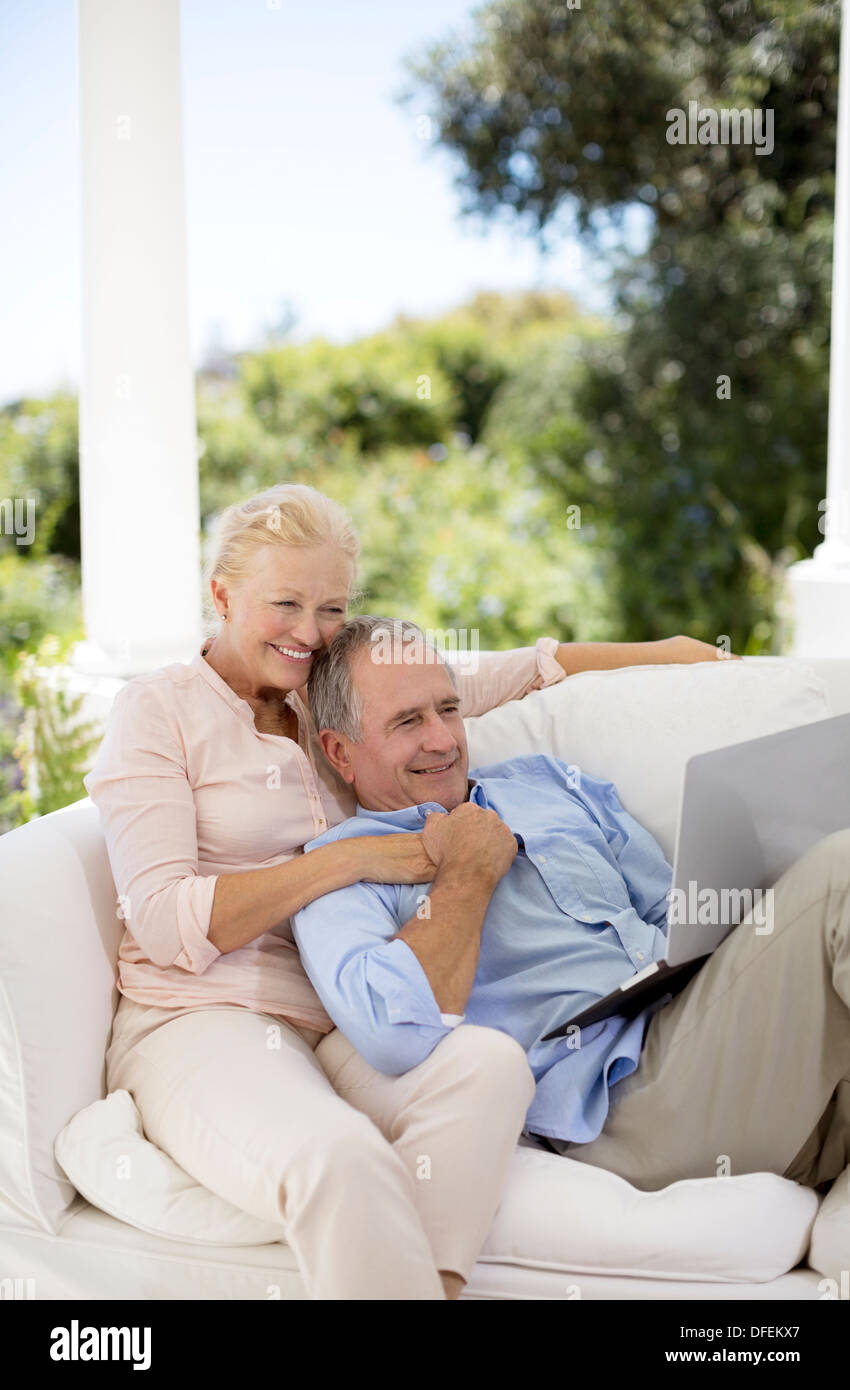 Senior couple using laptop on patio sofa - Stock Image