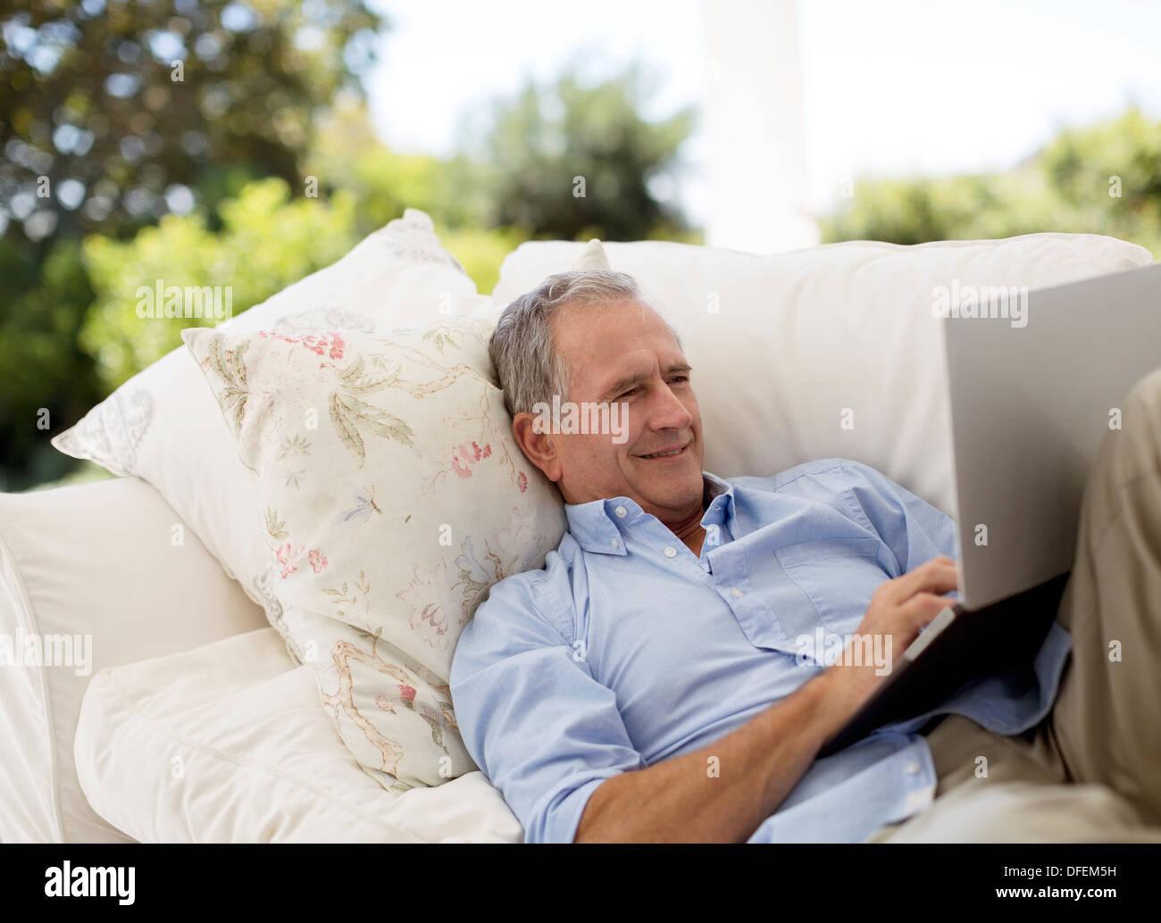 Senior man using laptop on patio sofa - Stock Image