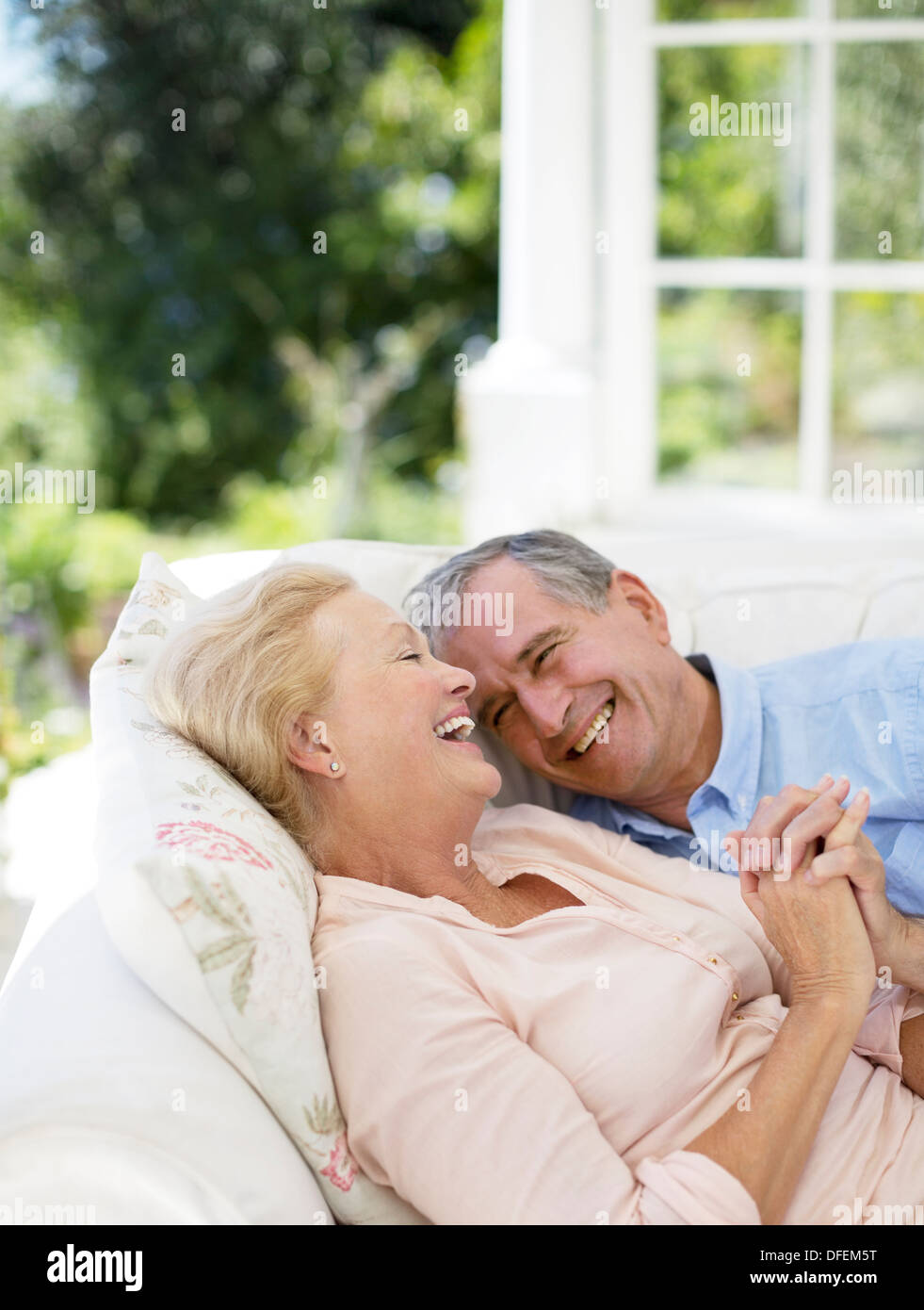 Senior couple laying on patio sofa and holding hands - Stock Image