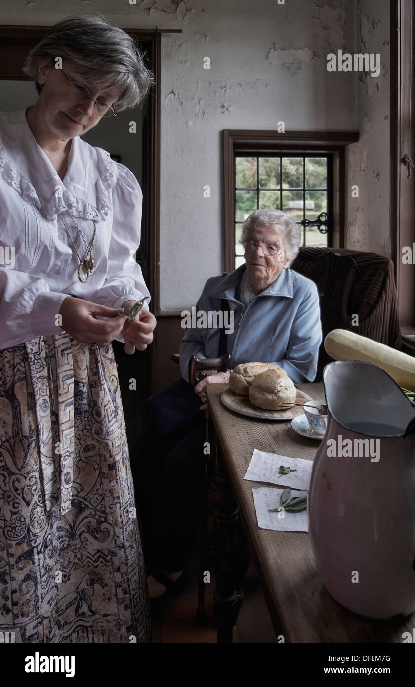Female employee of The Black Country Living Museum showing traditional food items from the 1800's/early 1900's era. England UK - Stock Image