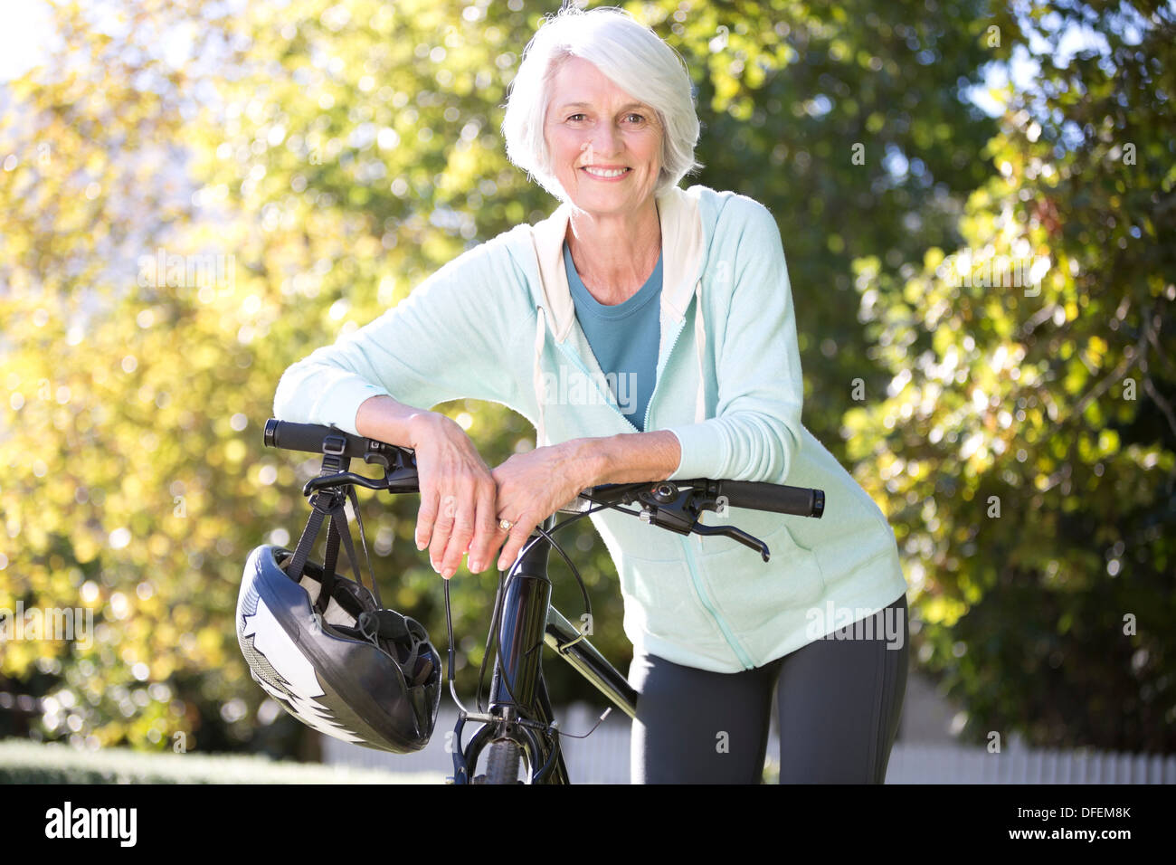 Portrait of senior woman leaning on bicycle - Stock Image