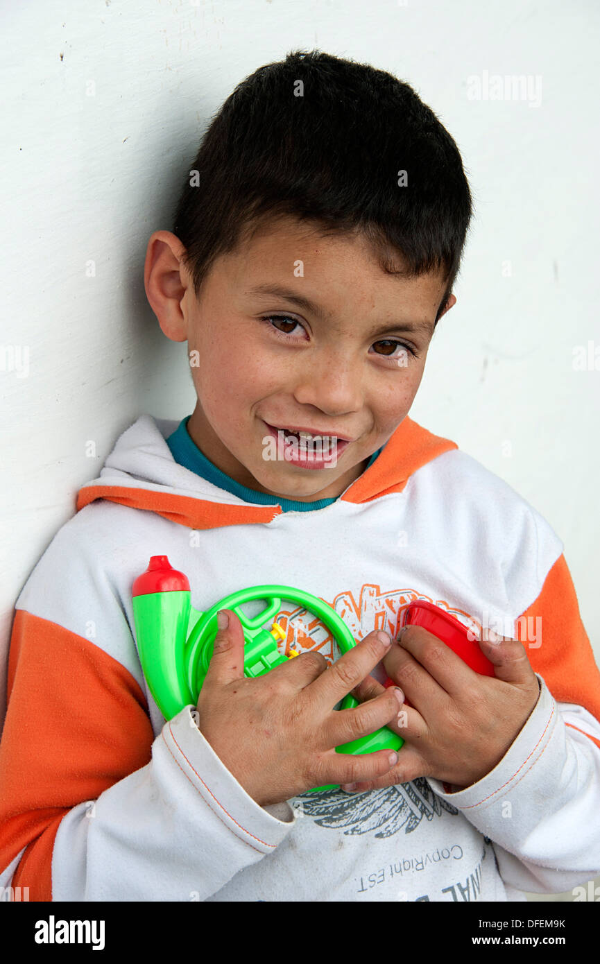 Young Colombian boy clutches plastic toy trumpet. El Juncal farm, Bogota. - Stock Image