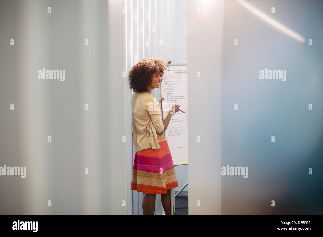 Businesswoman at whiteboard in conference room - Stock Image