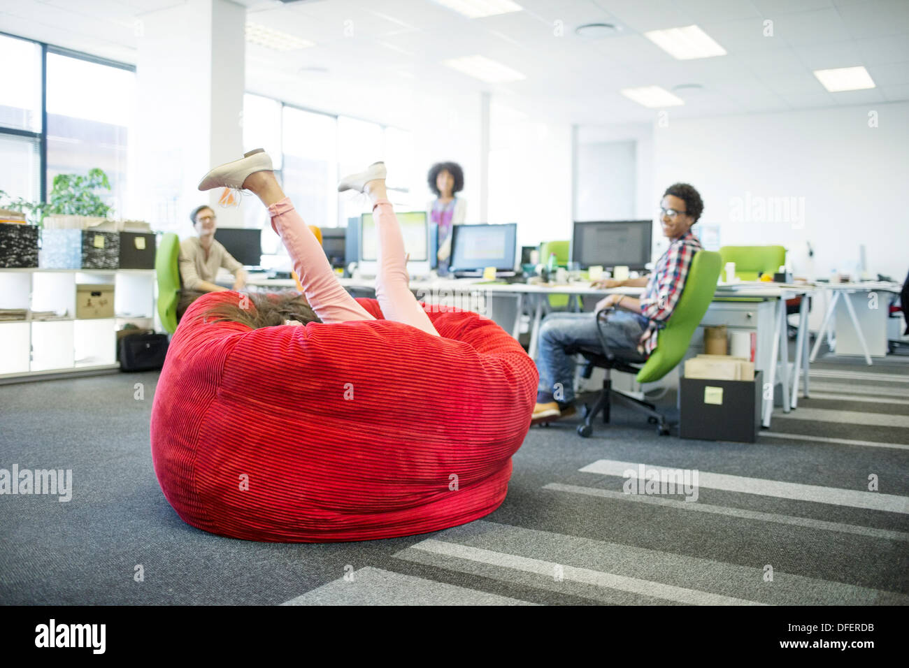 Businesswoman playing in beanbag chair in office - Stock Image
