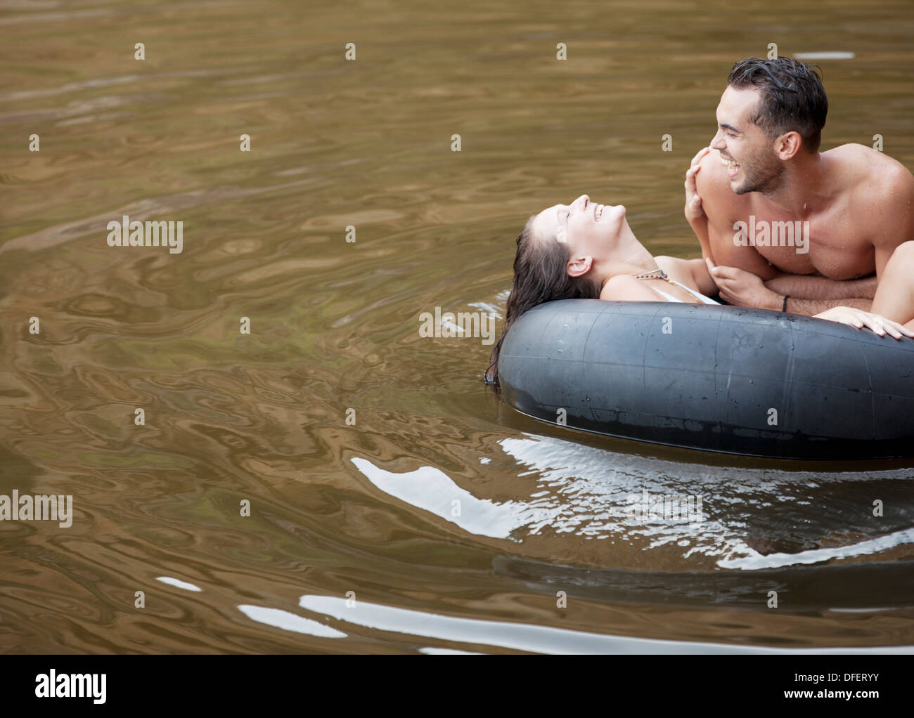 Couple playing in inner tube on lake - Stock Image
