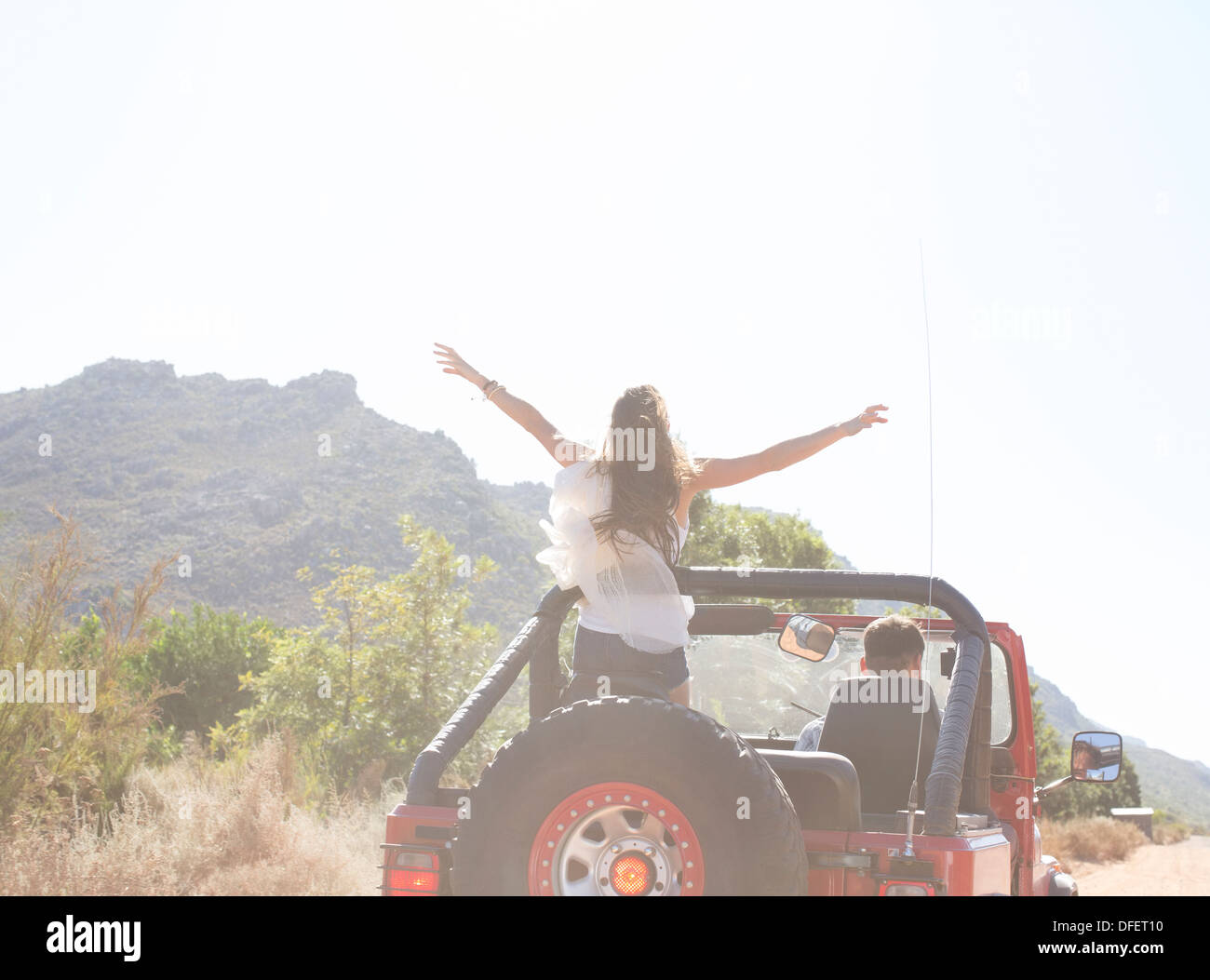 Woman standing in sport utility vehicle - Stock Image