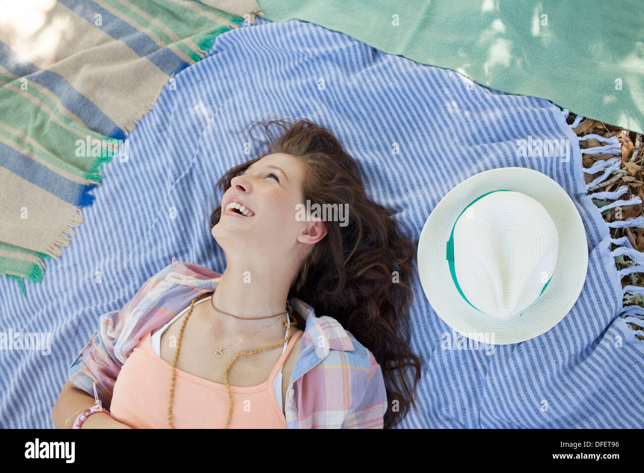 Woman laying on blanket outdoors - Stock Image