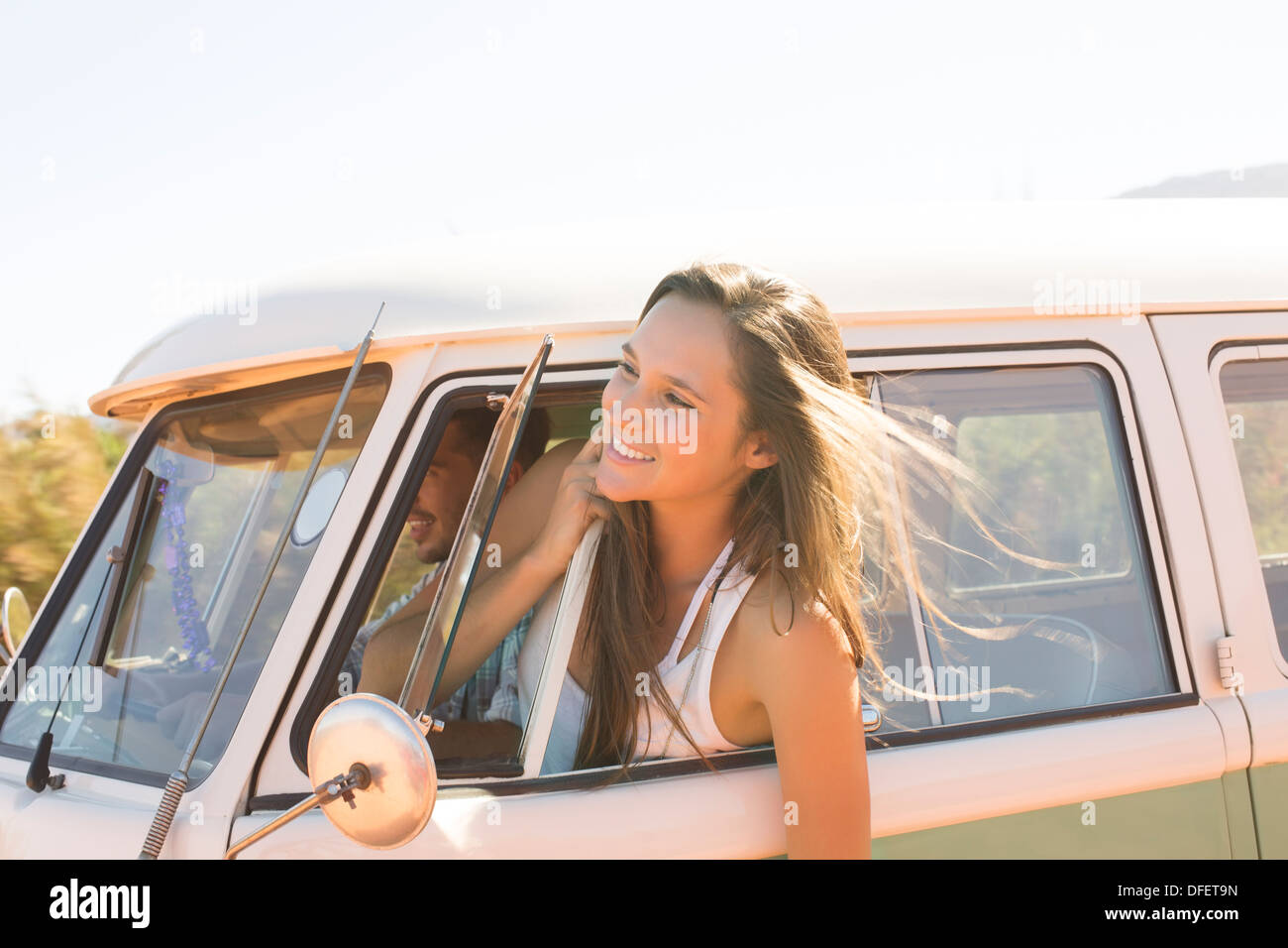 Woman leaning head out camper van window - Stock Image