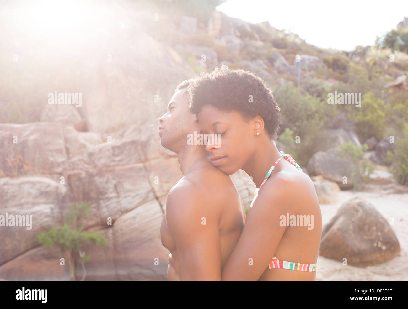 Couple hugging by rocks - Stock Image