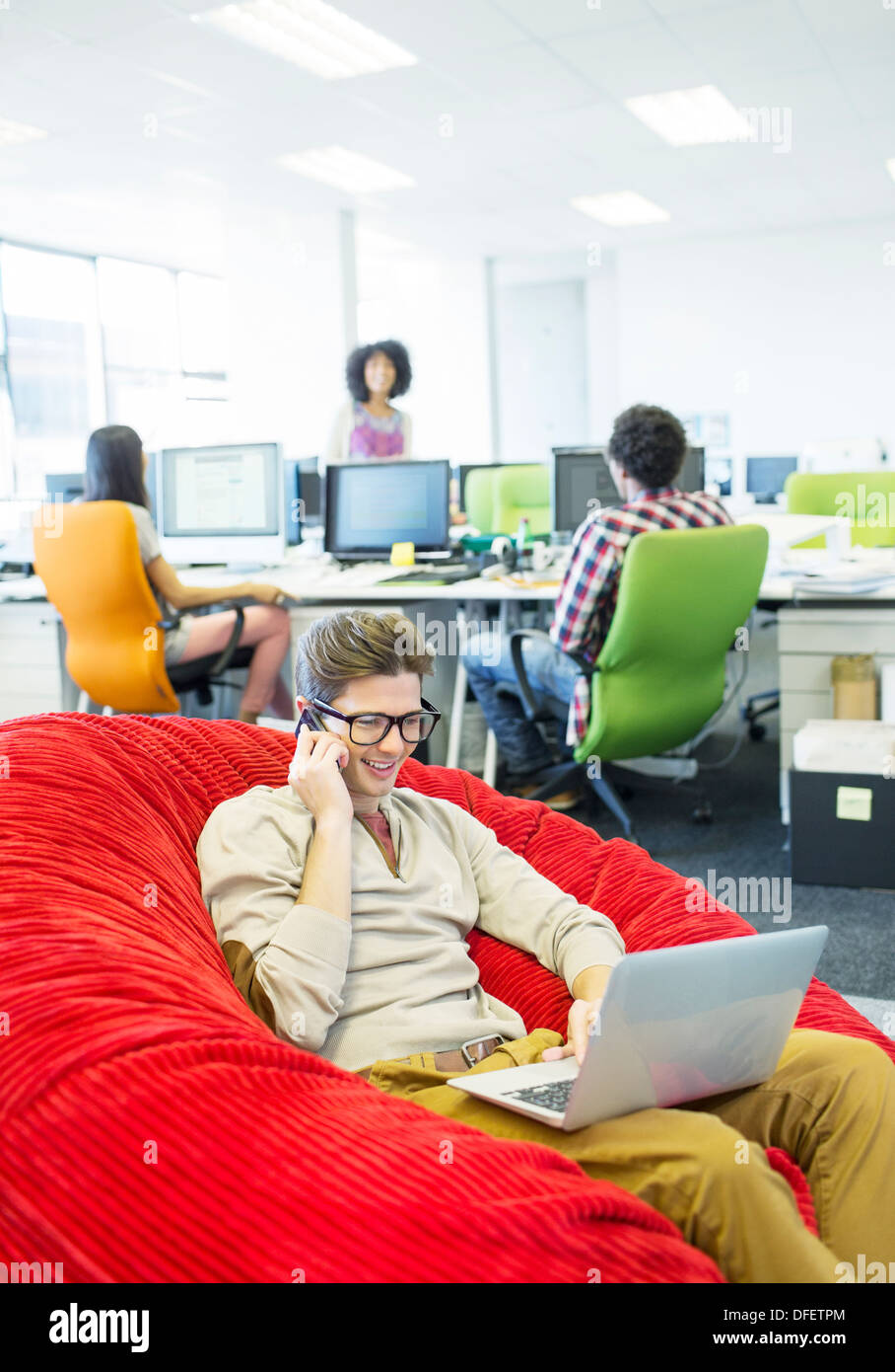 Businessman working in beanbag chair in office - Stock Image
