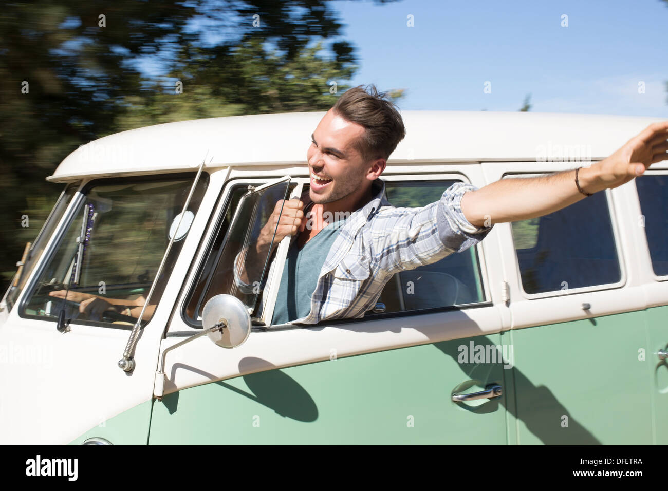 Man leaning head out camper van window - Stock Image