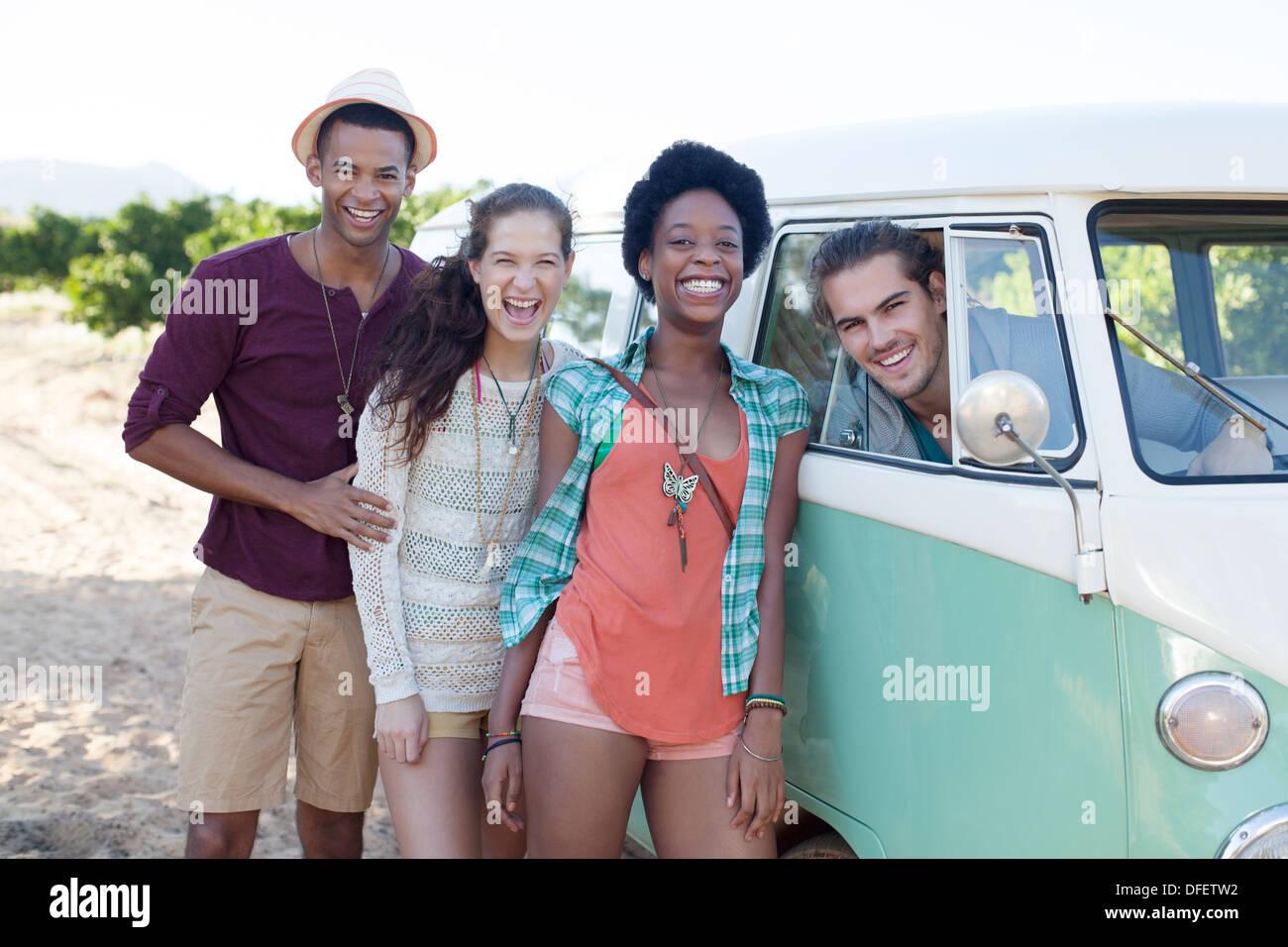 Friends laughing by camper van - Stock Image