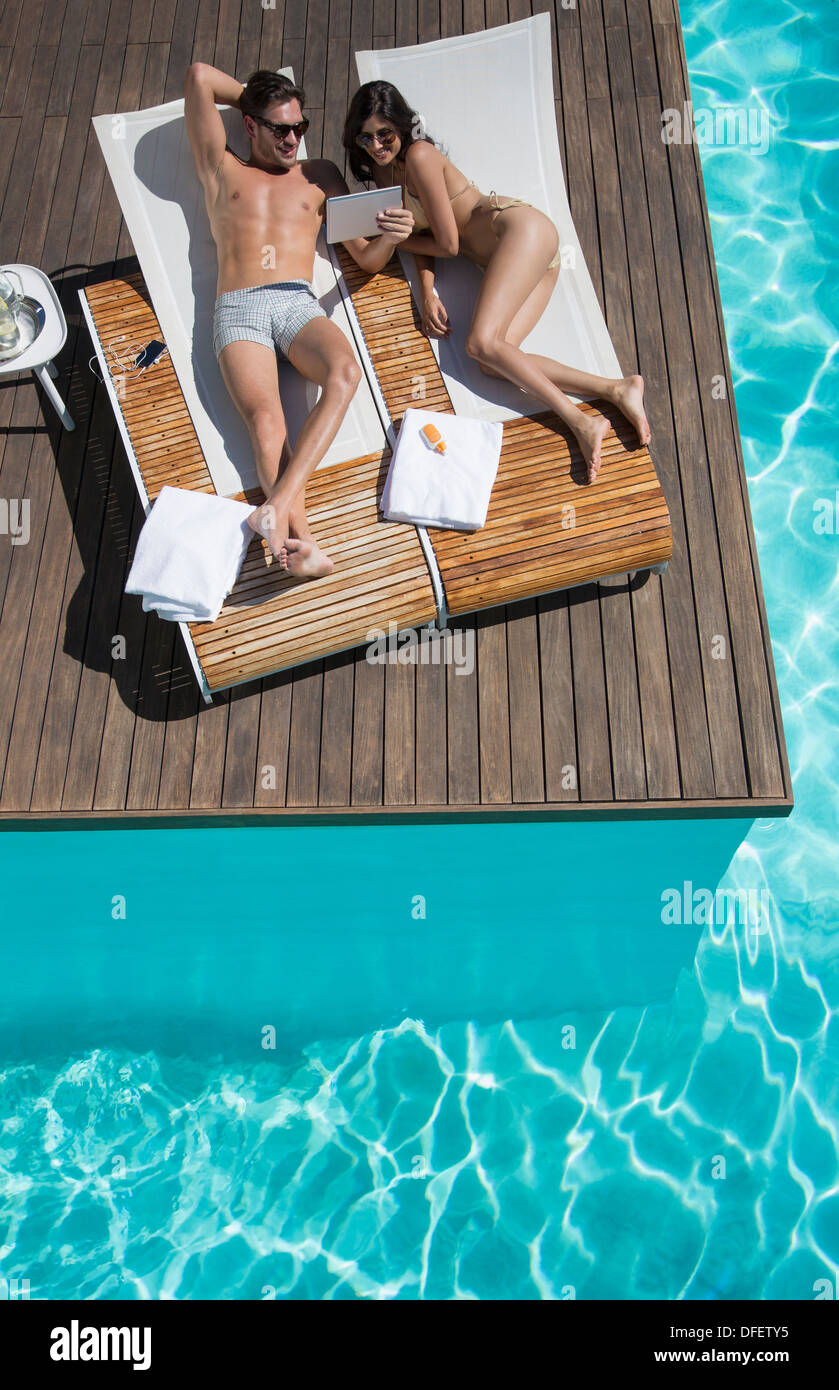 Couple relaxing on lounge chairs at poolside - Stock Image