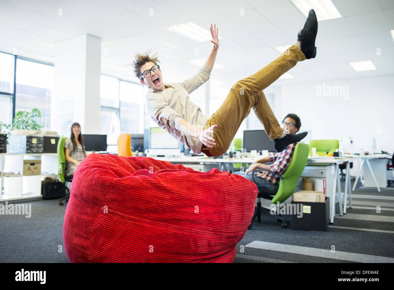 Businessman jumping into beanbag chair in office - Stock Image