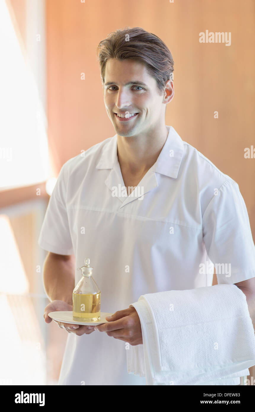 Masseuse carrying pitcher of oil at spa Stock Photo