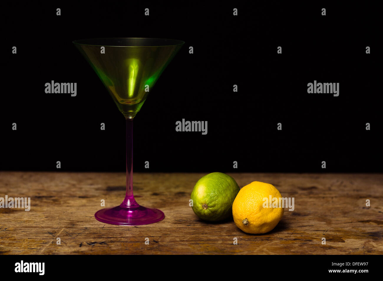 Lemon and lime next to a tall martini glass on wood surface Stock Photo