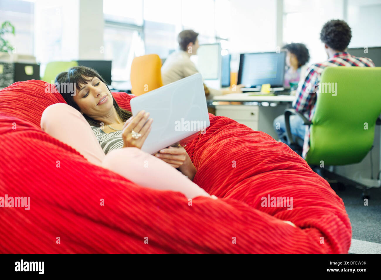 Businesswoman using laptop in bean bag chair in office - Stock Image