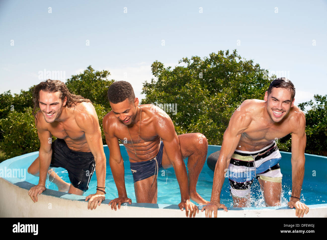 Men climbing out of swimming pool - Stock Image