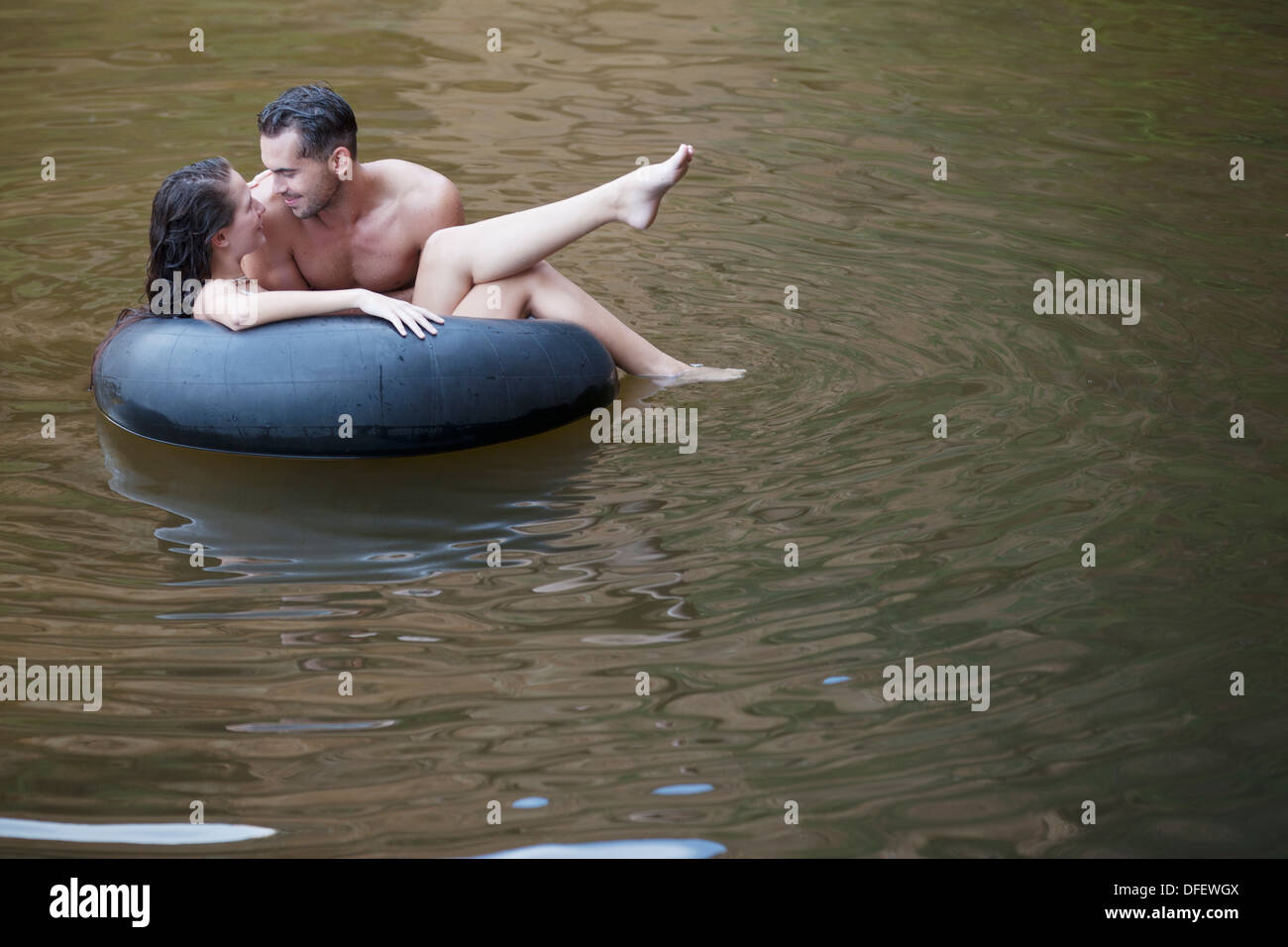 Couple playing in inner tube in river - Stock Image
