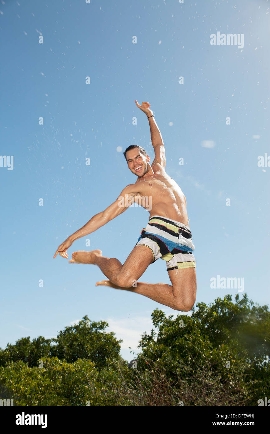 Man in swim trunks jumping - Stock Image