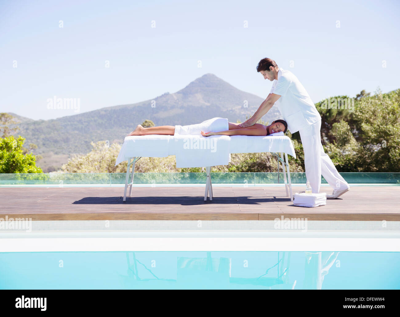 Woman receiving massage at poolside Stock Photo