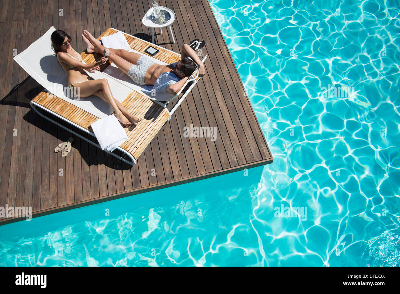 Brilliant Couple Laying On Lounge Chair At Poolside Stock Photo Ncnpc Chair Design For Home Ncnpcorg